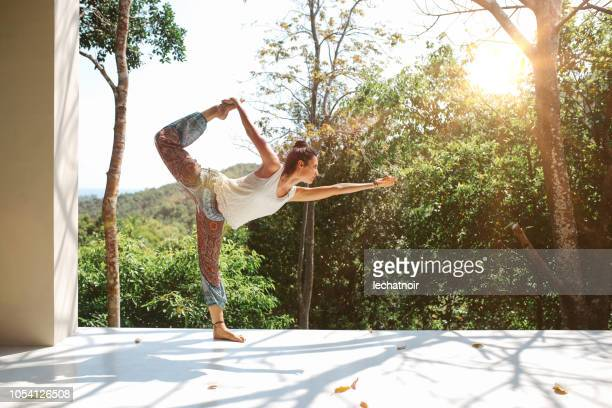young woman practicing natarajasana  lord of the dance pose in thailand - yogi stock photos and pictures