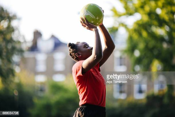 young woman practicing netball shooting in city - sporting term stock pictures, royalty-free photos & images