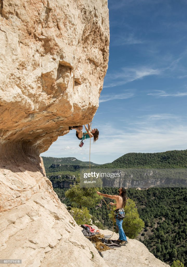 Young woman practicing rock climbing : Stock Photo