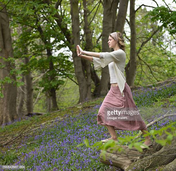 Young woman practicing Tai Chi in wood