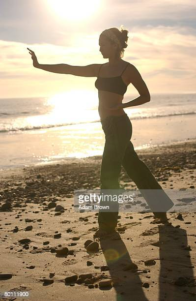 Young woman practicing Tai Chi on beach at sunset