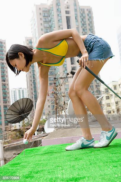 Young Woman Practicing Teeing Off on Apartment Block Roof