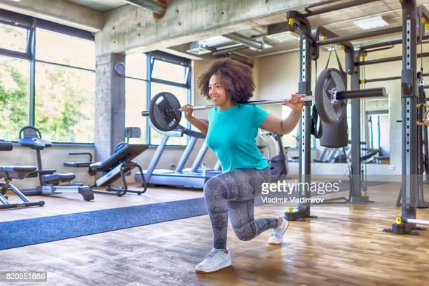 jovem mulher praticando com halteres no ginásio - vara - fotografias e filmes do acervo