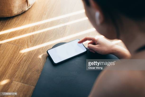 young woman practicing yoga and using smartphone at home - looking over shoulder stock pictures, royalty-free photos & images