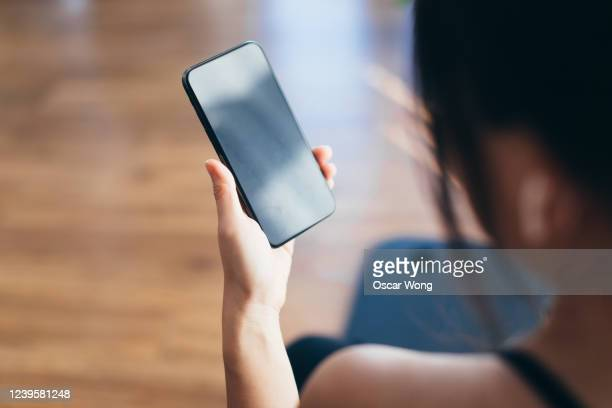 young woman practicing yoga and using smartphone at home - smart phone stock pictures, royalty-free photos & images