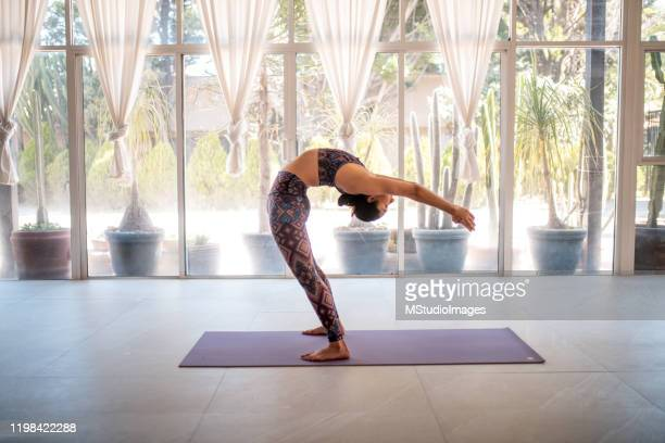 young woman practicing yoga at a studio - yogi stock pictures, royalty-free photos & images