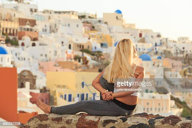 Young woman practicing yoga at beautiful Santorini Greece