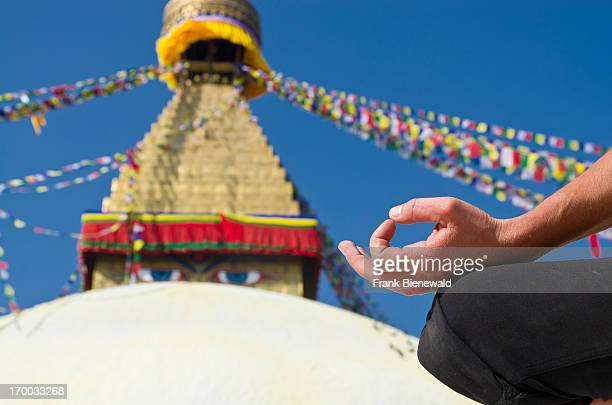 Young woman practicing yoga at Boudnath Stupa showing the pose chin mudra / om mudra Boudnath with its huge Stupa is the center for Buddhist pilgrims...