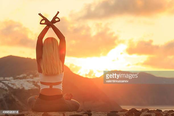 Young woman practicing yoga at golden sunset in Santorini Greece