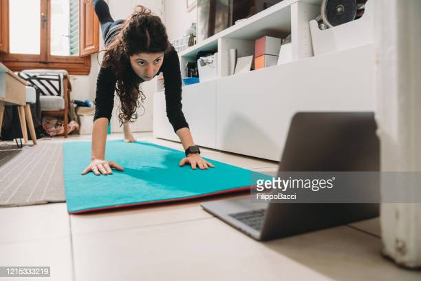 young woman practicing yoga at home - isolamento foto e immagini stock