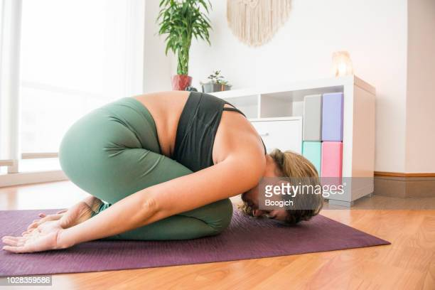 young woman practicing yoga at home resting in child's pose miami usa - childs pose stock photos and pictures