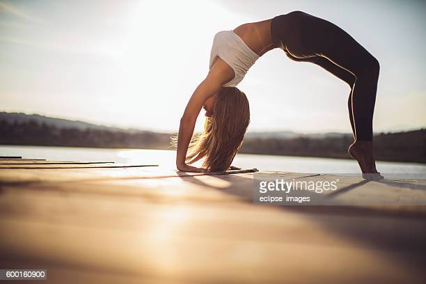 Young woman practicing yoga at lake
