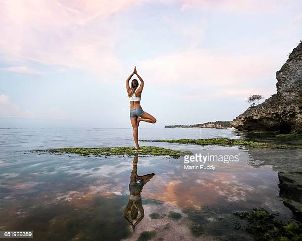 young woman practicing yoga at seashore
