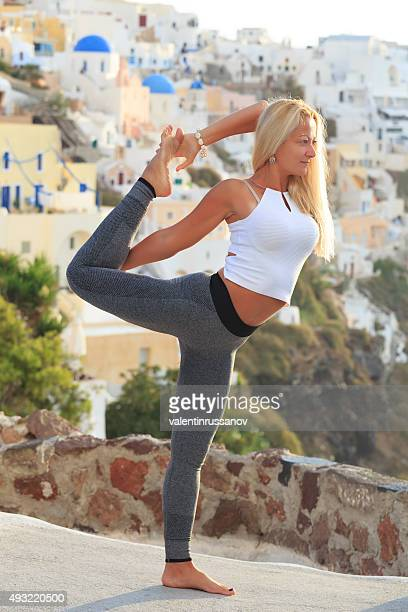 Young woman practicing yoga at sunset in Santorini Greece
