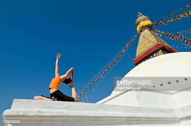 A young woman practicing yoga at the Boudnath Stupa showing the pose kapotasana dove pose / pigeon pose Boudnath with its huge Stupa is the center...
