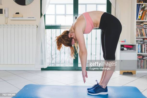 young woman practicing yoga bending forward on yoga mat - bending over stock pictures, royalty-free photos & images