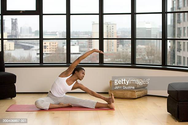 Young woman practicing yoga, cityscape in background