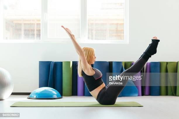 junge frau praktizieren yoga in ein fitness-studio, boot-pose. - sportlerin stock-fotos und bilder