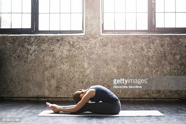 Young woman practicing yoga in an urban loft