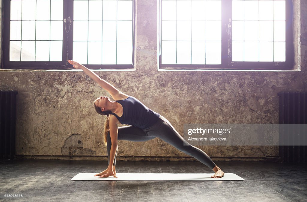 Young woman practicing yoga in an urban loft : ストックフォト