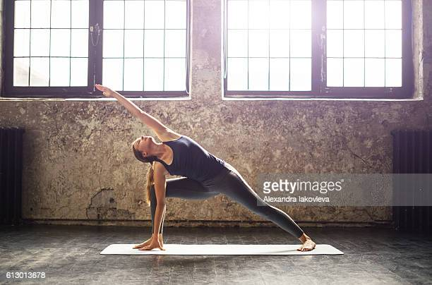 young woman practicing yoga in an urban loft - yoga stockfoto's en -beelden