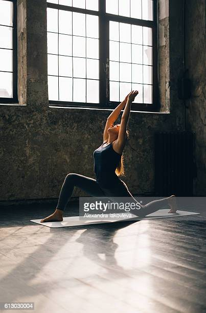 young woman practicing yoga in an urban loft - yoga teacher stock pictures, royalty-free photos & images