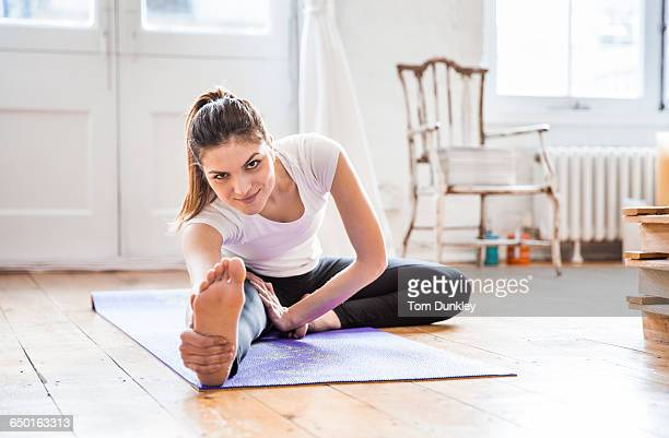 Young woman practicing yoga in apartment, touching toes