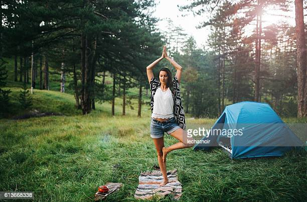 Young woman practicing yoga in front of the tent