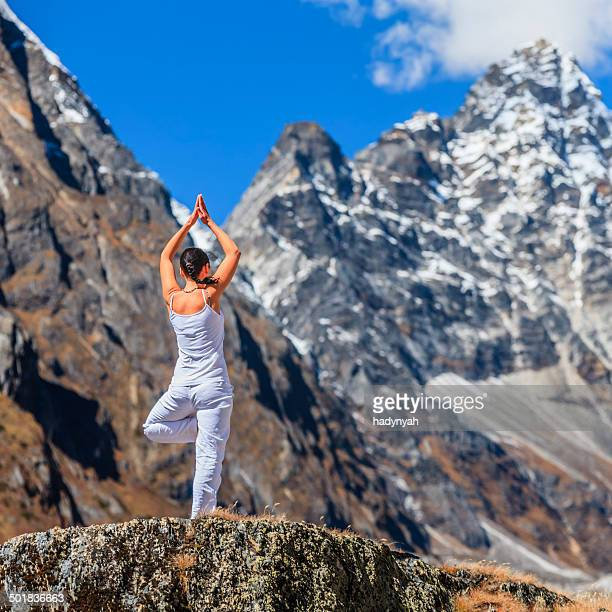 Young woman practicing yoga in Himalayas, Mount Everest National Park