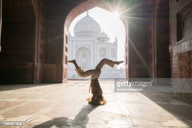 young woman practicing yoga in india at the famous taj mahal at sunrise - headstand position upside down- people travel spirituality zen like concept - india stock pictures, royalty-free photos & images