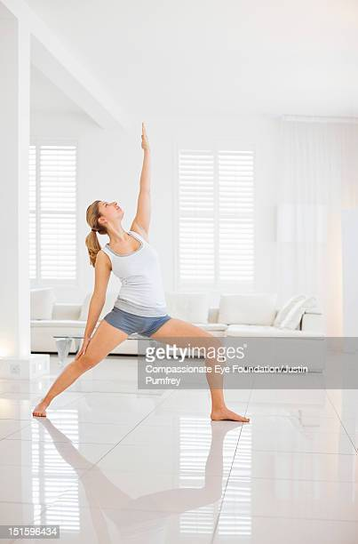 Young woman practicing yoga in living room