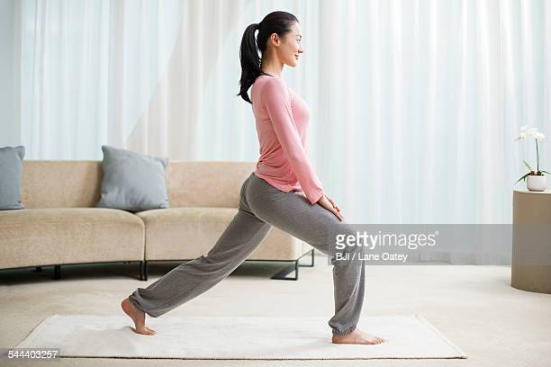 young woman practicing yoga in living room - only young women stock pictures, royalty-free photos & images
