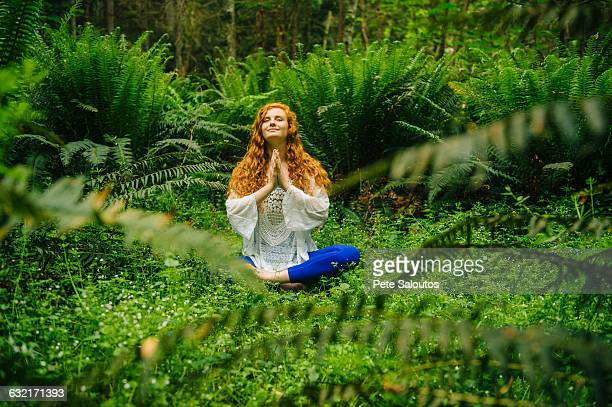 young woman practicing yoga in lotus position in forest - zen like stock pictures, royalty-free photos & images