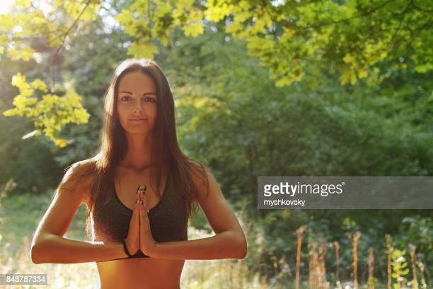 Young woman practicing yoga in the forest