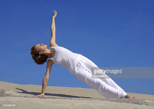 Young woman practicing yoga in the side plank pose
