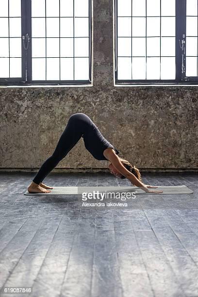 Young woman practicing yoga in urban loft: downward facing dog