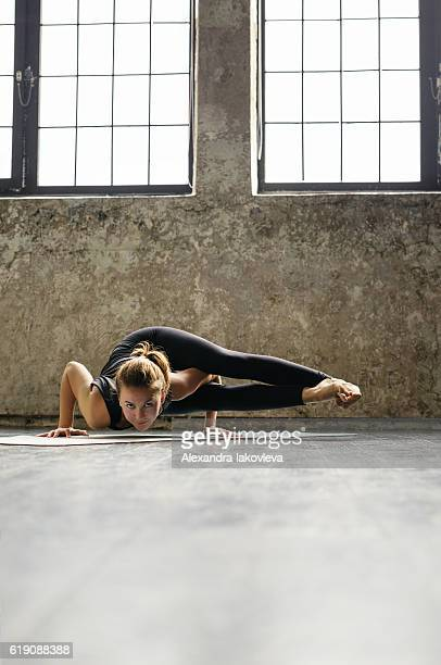 Young woman practicing yoga in urban loft: Eight-Angle Pose