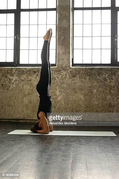Young woman practicing yoga in urban loft: Salamba Sirsasana pose