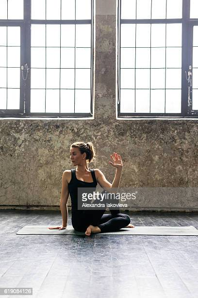 Young woman practicing yoga in urban loft: spinal twist pose