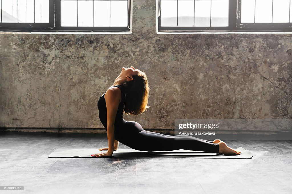 Young woman practicing yoga in urban loft: Upward Facing Dog : Stock Photo