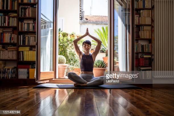 jovem praticando yoga em chamada de vídeo de casa - bem estar - fotografias e filmes do acervo