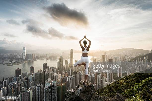young woman practicing yoga infront of Hong Kong