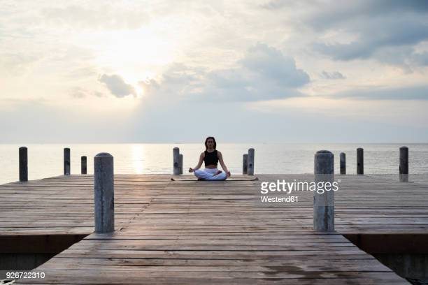 young woman practicing yoga on a jetty by the sea at sunset - yogi stock photos and pictures