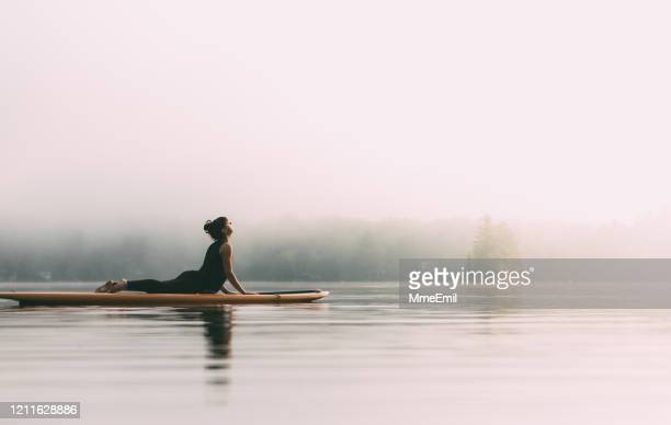 young woman practicing yoga on a paddleboard - mmeemil stock pictures, royalty-free photos & images