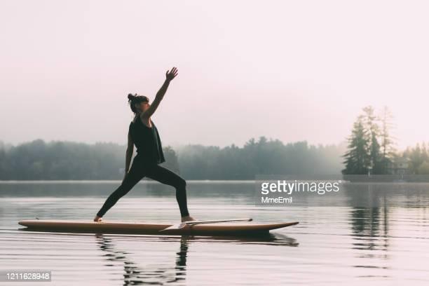 giovane donna che pratica yoga su un paddleboard - equilibrio foto e immagini stock