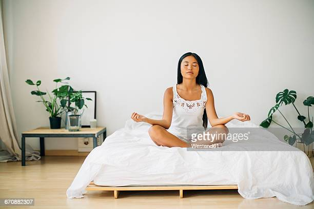 Young woman practicing yoga on bed