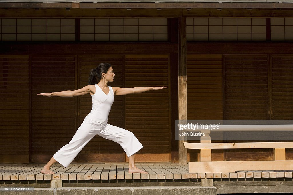 Young woman practicing yoga on deck in Japanese garden : Foto stock