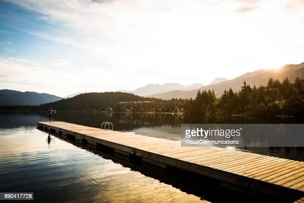 jeune femme de pratiquer l'yoga sur le quai au bord du lac. - bonne posture photos et images de collection