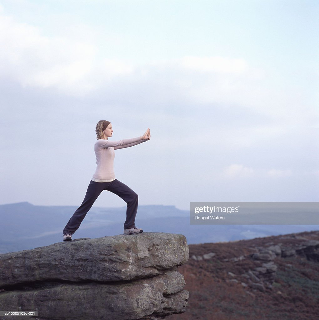 Young woman practicing yoga on rock edge : ストックフォト