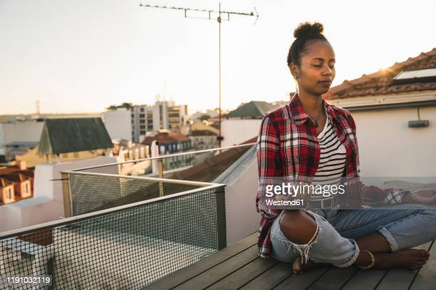 young woman practicing yoga on rooftop at sunset - lotus position stock pictures, royalty-free photos & images